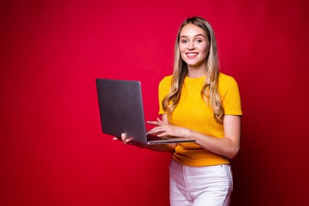 Portret u? miechni? te m? ode kobiety gospodarstwa, pracuj? c na komputerze typu laptop pc odizolowane na czerwonej? cianie.