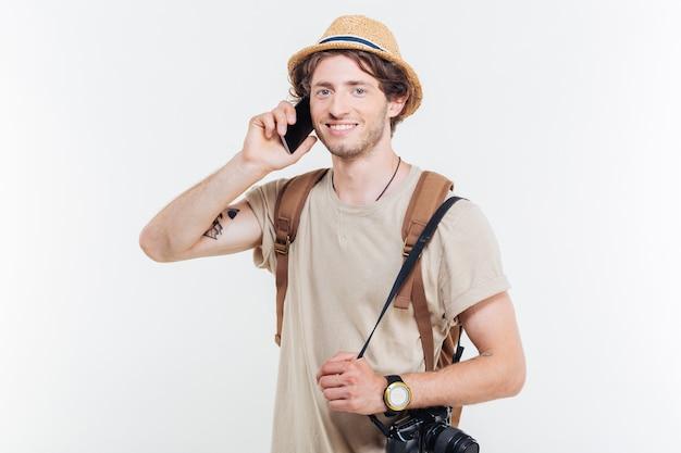 Portret u? miechni? tego m? odego cz? owieka z plecakiem i aparatem podczas rozmowy telefonicznej na bia? ym tle