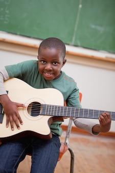 Portret uczeń bawić się gitarę