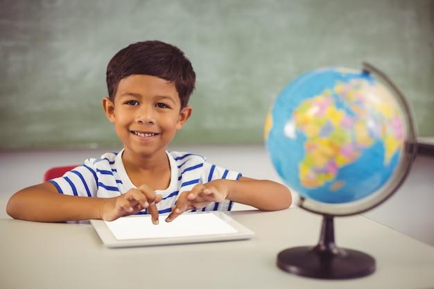 Portret uczeń używa cyfrową pastylkę w sala lekcyjnej