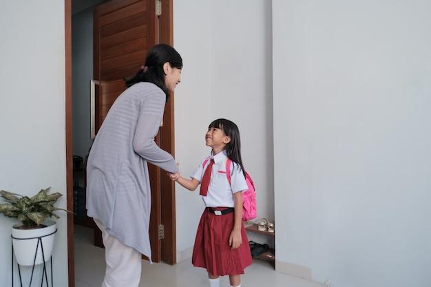 Portret uczennicy indonezyjskiej szkoły podstawowej potrząsa i całuje rękę matki przed pójściem do szkoły