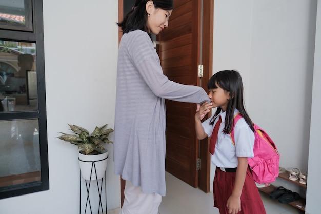Portret uczennicy indonezyjskiej szkoły podstawowej trzęsie się i całuje rękę matki przed pójściem do szkoły