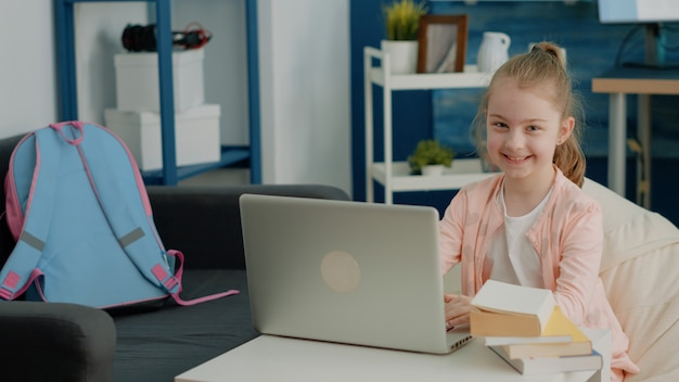 Portret uczennicy korzystającej z laptopa na lekcjach szkolnych online