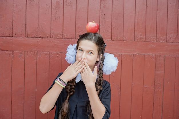 Portret uczennicy pozycja z jabłkiem na głowie