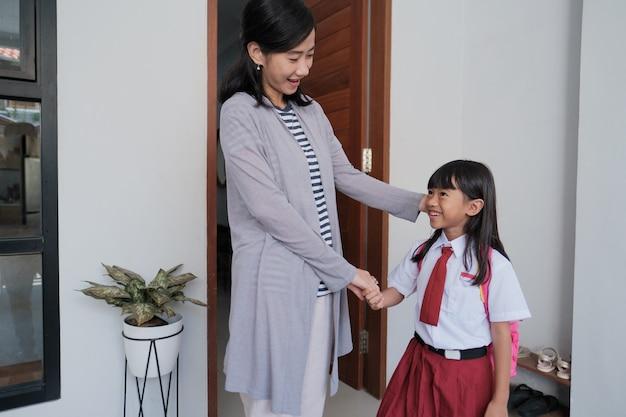 Portret uczennicy z indonezyjskiej szkoły podstawowej, przed pójściem do szkoły, podaje matce dłoń