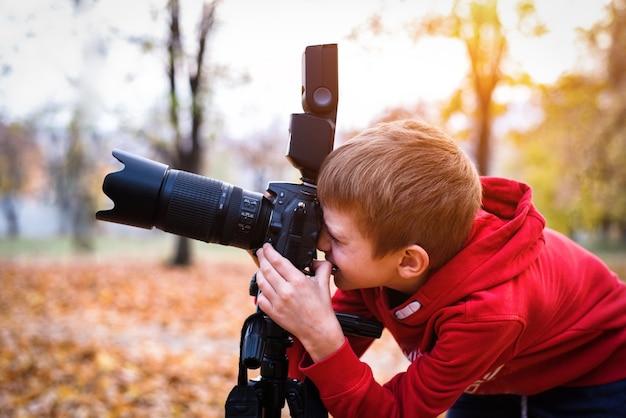 Portret ucznia robi zdjęcia lustrzanką. jesienny park