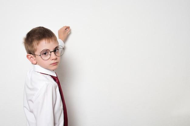 Portret ucznia w okrągłych okularach. udaje, że pisze na tablicy. białe tło.