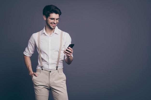 Portret udanego biznesu człowiek dobry nastrój trzymając się za ręce telefon czytać służbowy adres e-mail ubrany wizytowe koszula szelki spodnie specyfikacje.