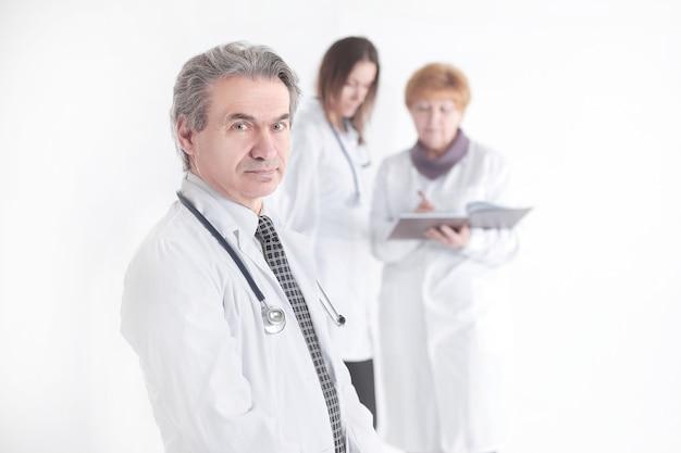 Portret udanego lekarza terapeuty na niewyraźnym tle kolegów