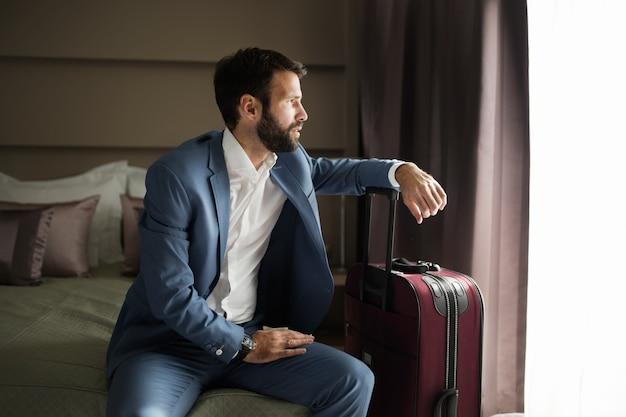 Portret udanego młodego biznesmena siedzącego w pokoju hotelowym