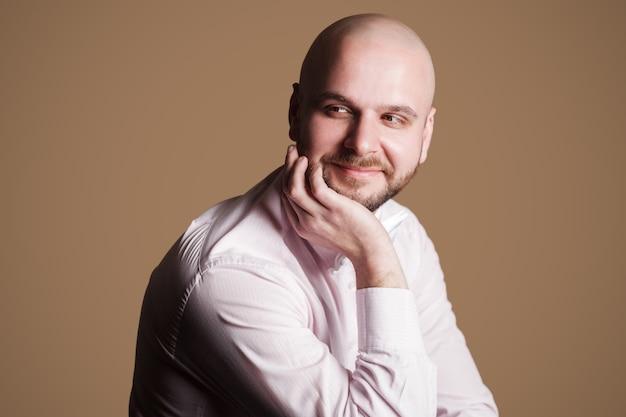 Portret udanego przystojny brodaty łysy mężczyzna w jasnoróżowej koszuli i białej kokardce, siedząc na krześle i odwracając się z uśmiechniętą twarzą i rozmyślając. kryty strzał studio, na białym tle na brązowym tle.