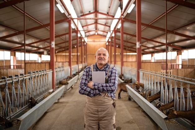 Portret udanego starszego pracownika farmy farmera stojącego w stajni kóz i trzymając tablet.