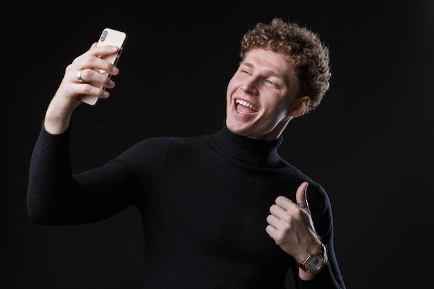 Portret udanego wesołego młodego atrakcyjnego biznesmena z kręconymi włosami stojącego przed czarną ścianą, biorącego selfie, dającego kciuk w górę