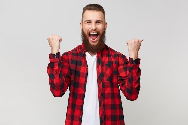 Portret udanego wesołego szczęśliwego szczęśliwego brodatego mężczyzny w kraciastej koszuli zaciskającej pięści jak zwycięzca, świętuje swoje zwycięstwo, odizolowany na białym tle