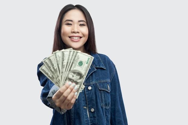 Portret udanej atrakcyjnej młodej dziewczyny azjatyckiej w stojącej niebieskiej kurtce dżinsowej, trzymającej wiele dolarów, demonstracji i patrząc na kamerę z uśmiechem. wewnątrz, studio strzał, na białym tle, szare tło