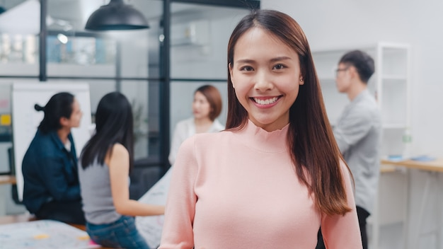Portret udanej pięknej bizneswoman wykonawczej inteligentnego noszenia na co dzień, patrząc na kamerę i uśmiechając się
