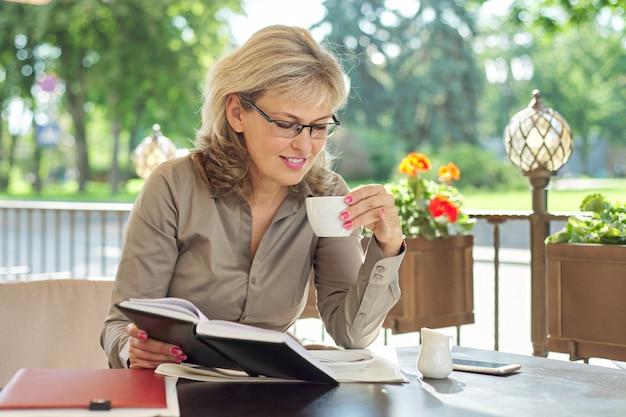 Portret udanej pięknej blond kobieta w średnim wieku w letniej restauracji na świeżym powietrzu. kobieta ma przerwę na kawę