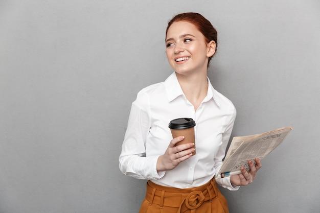 Portret udanej rudowłosej bizneswoman 20s ubranej w strój wizytowy, pijącej kawę na wynos i czytającej gazetę w biurze na białym tle nad szarym