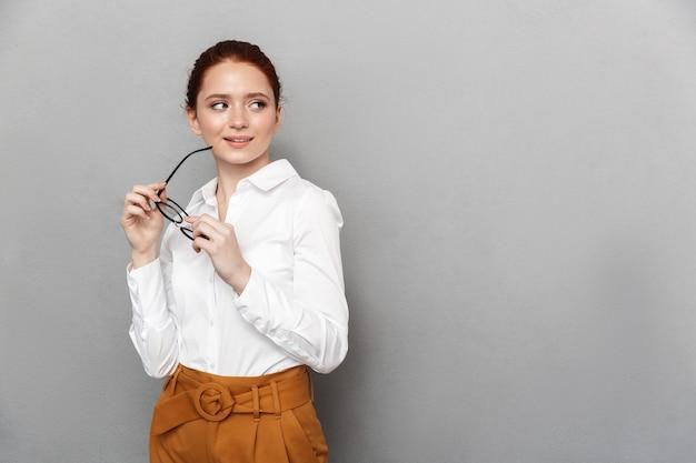 Portret udanej rudowłosej bizneswoman 20s w formalnym stroju, trzymającej okulary i uśmiechającej się w biurze odizolowanym nad szarym