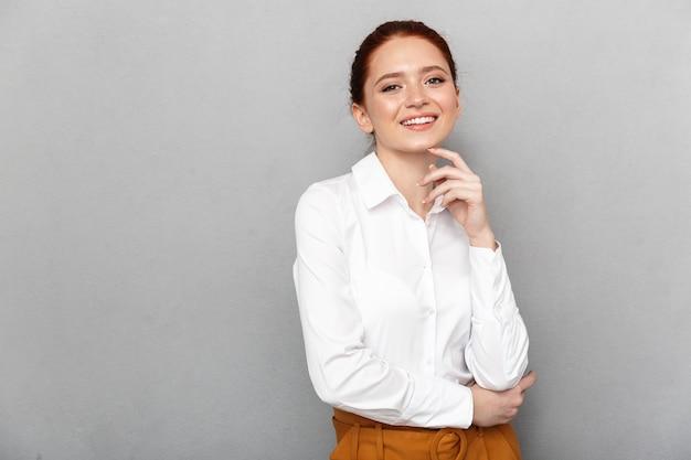 Portret udanej rudowłosej bizneswoman 20s w formalnym stroju, uśmiechniętej i pozującej w biurze na białym tle nad szarym