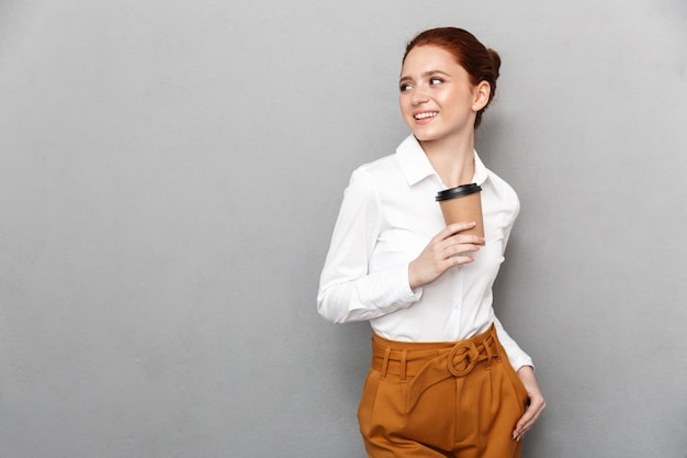 Portret udanej rudowłosej bizneswoman 20s w stroju wizytowym, uśmiechający się w biurze i pijący kawę na wynos z plastikowego kubka izolowanego nad szarością
