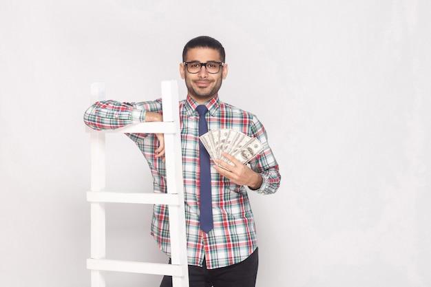 Portret udany bogaty przystojny brodaty młodzieniec w kolorowe kraciaste koszule z niebieskim krawatem stojący, trzymając wentylator gotówki i chudego na białych schodach. kryty strzał studio, na białym tle na szarym tle