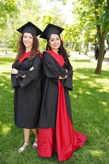 Portret udanych absolwentów noszenia czapki na zewnątrz w pobliżu uniwersytetu