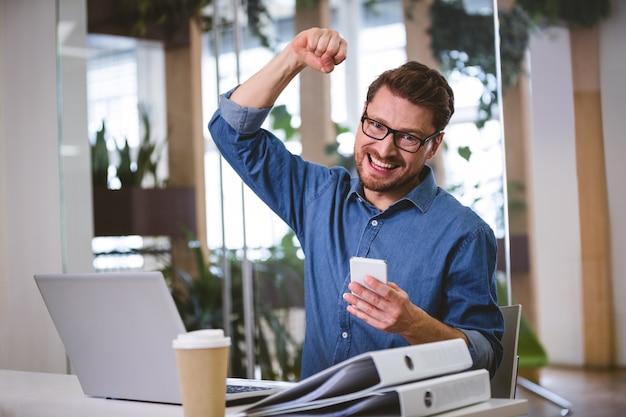 Portret uderza pięścią w powietrzu przy biurem z podnieceniem biznesmen