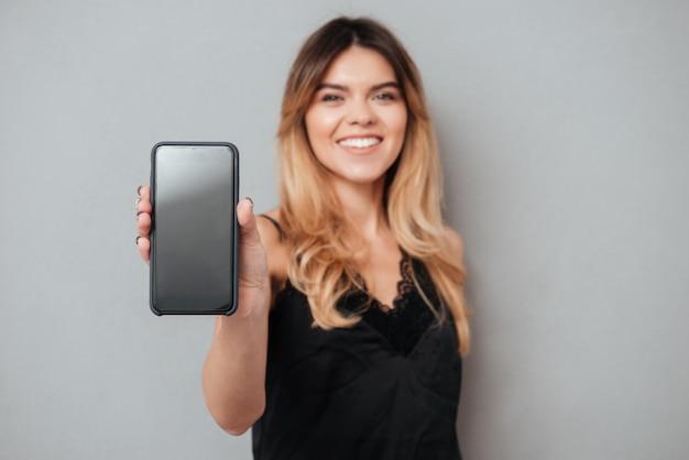 Portret ufna kobieta pokazuje pustego ekranu telefon komórkowego