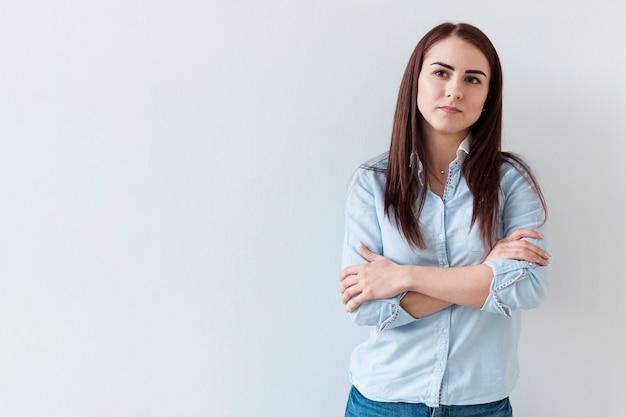 Portret ufna kobieta z przecinającymi rękami