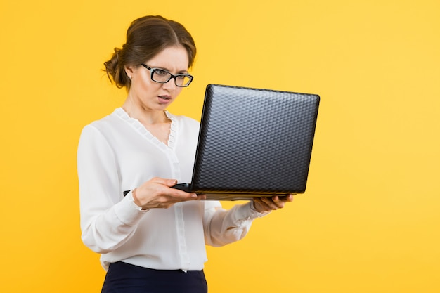 Portret ufna piękna intrygująca młoda biznesowa kobieta pracuje na laptopie na kolorze żółtym