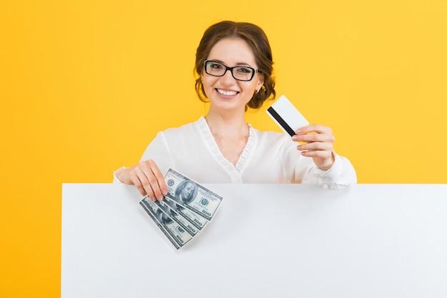 Portret ufna piękna młoda biznesowa kobieta z pieniądze i kredytową kartą w jej rękach z pustym billboardem na kolorze żółtym