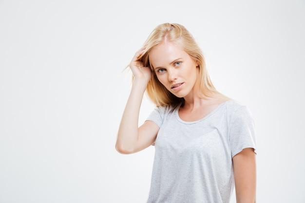 Portret ufna piękna młoda kobieta z blond włosami na białej ścianie