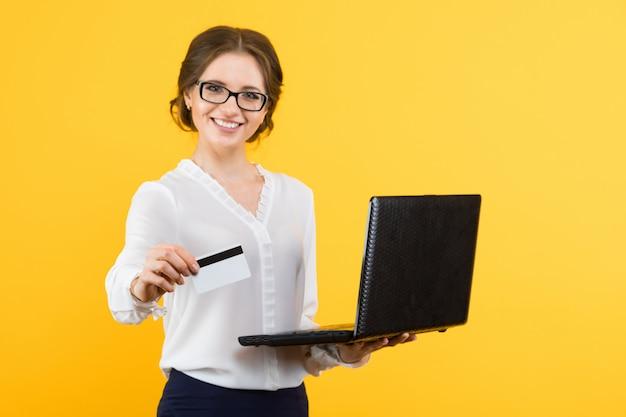 Portret ufna piękna młoda uśmiechnięta biznesowa kobieta oferuje kredytową kartę z laptopem
