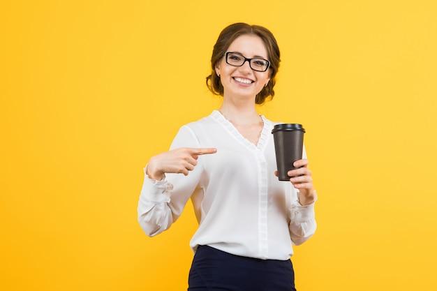 Portret ufna piękna młoda uśmiechnięta szczęśliwa biznesowa kobieta pokazuje na filiżance kawy z jej ręką na kolorze żółtym