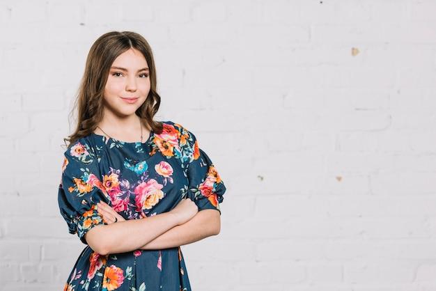 Portret ufna uśmiechnięta nastoletniej dziewczyny pozycja przeciw ścianie