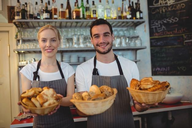 Portret ufni pracownicy z świeżym chlebem w koszach