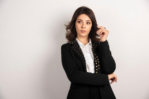 Portret ufny bizneswoman pozuje na bielu.