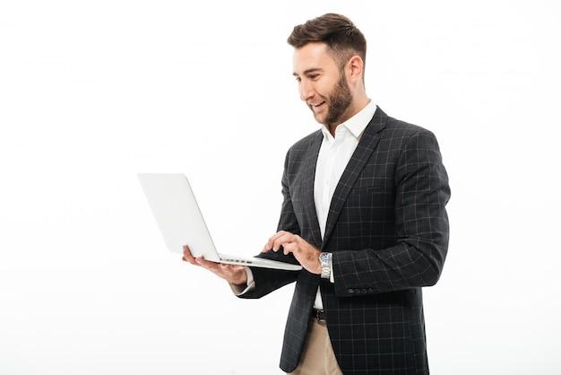 Portret ufny brodaty mężczyzna używa laptop