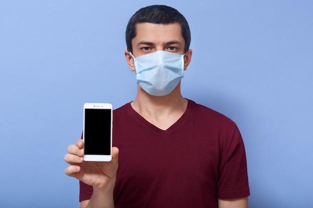 Portret ufny młodego człowieka mienia smartphone z pustym ekranem w jeden ręce, będący ubranym twarzową maskę ochraniać przed koronawirusa covid19 pojęciem.