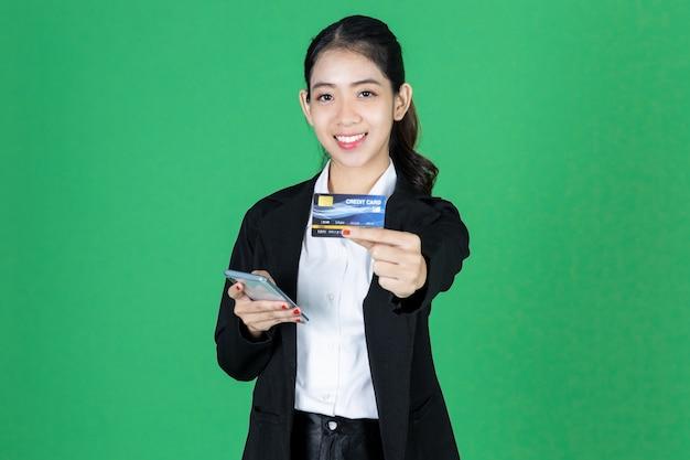 Portret ufny młody azjatykci bizneswoman z kredytową kartą i smartphone