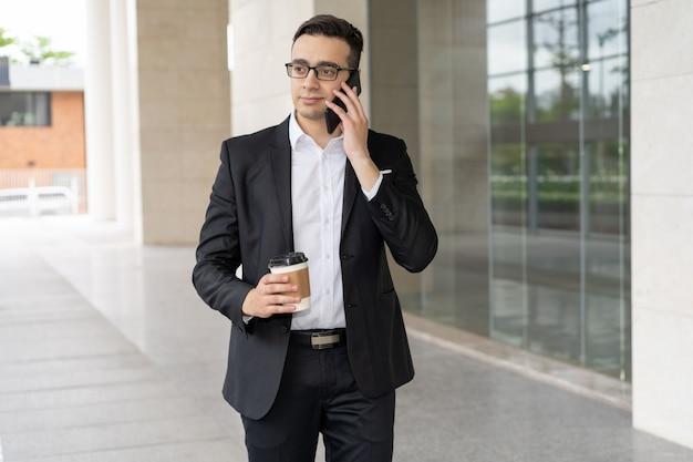 Portret ufny młody biznesmen opowiada na telefonie komórkowym