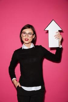 Portret ufny młody bizneswoman wskazuje up z strzała