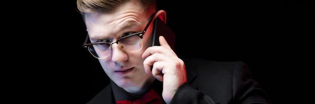 Portret ufny przystojny ambitny szczęśliwy elegancki odpowiedzialny biznesmen opowiada na telefonie na czarnym tle