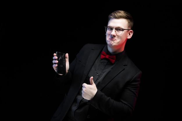 Portret ufny przystojny ambitny szczęśliwy elegancki odpowiedzialny biznesmen pokazuje na telefonie komórkowym na czarnym tle