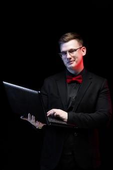 Portret ufny przystojny ambitny szczęśliwy elegancki odpowiedzialny biznesmen pracuje na jego laptopie na czerni