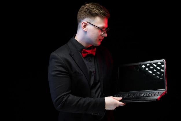 Portret ufny przystojny ambitny szczęśliwy elegancki odpowiedzialny biznesmen pracuje na jego laptopie