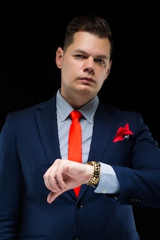 Portret ufny przystojny biznesmen ogląda jego czas na czarnym tle