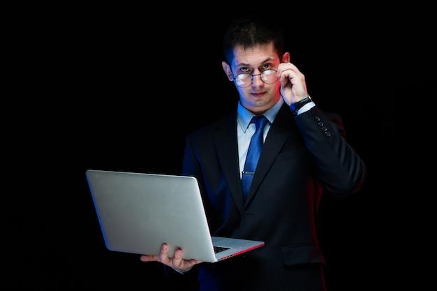 Portret ufny przystojny elegancki biznesmena mienia laptop w jego rękach na czarnym tle
