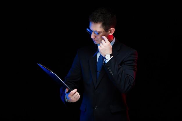 Portret ufny przystojny elegancki biznesmena mienia schowek w jego rękach na czarnym tle